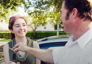 parent handing over car key to teenager