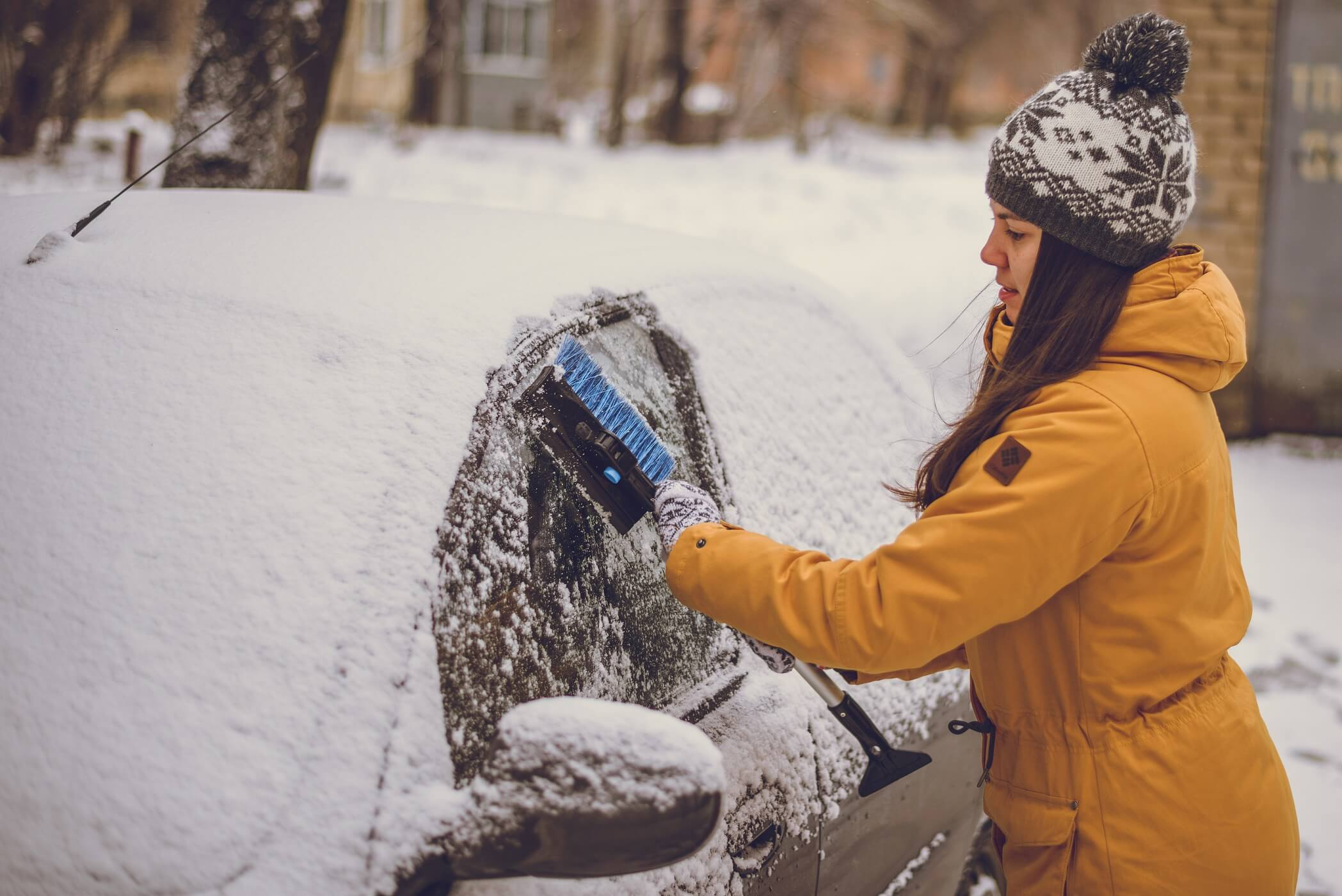 Woman cleaning car windshield of snow winter happy young scraper